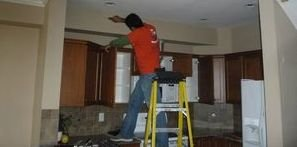 Technician Cleaning Mold Off of Ceiling After Ceiling Leak
