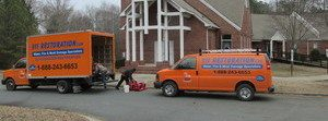 Water Damage Restoration Van And Truck Parked At Residential Job Site