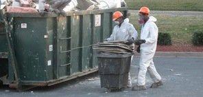 Water Damage Restoration Technicians Removing Debris To Street Dumpster